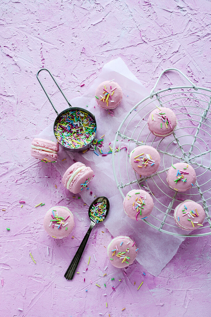 Basic macarons colored in pink and decorated with sprinkles