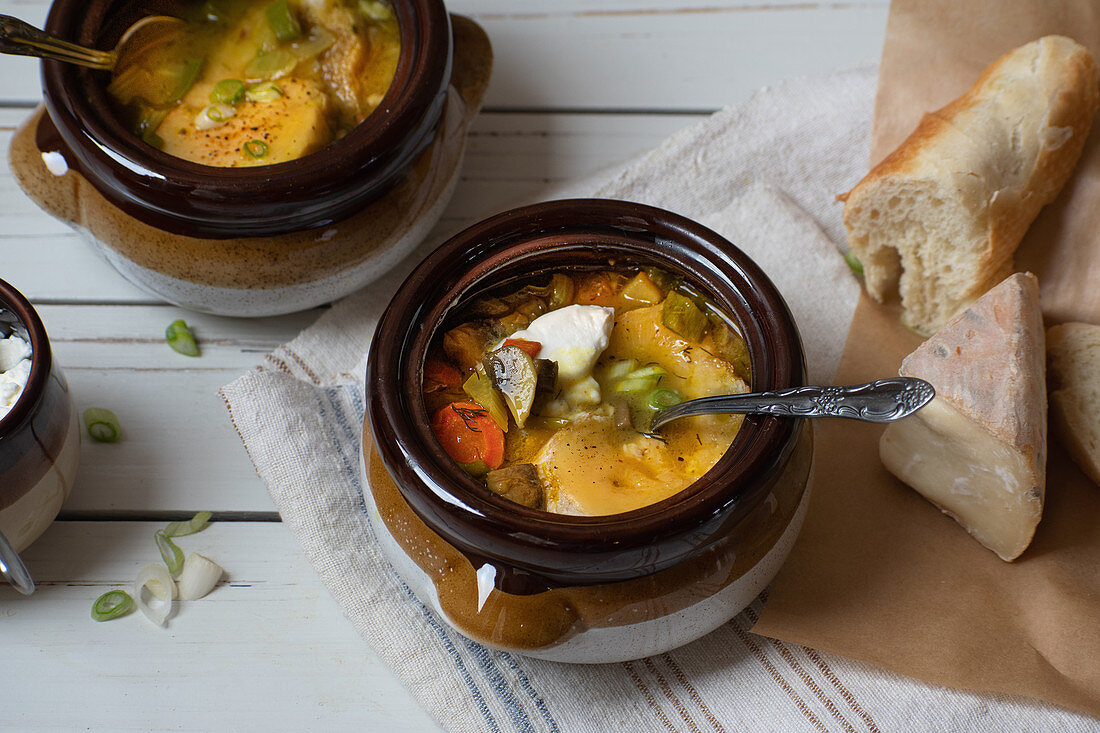 Mixed vegetable soup served in clay pots, topped with grilled cheese and bread toast