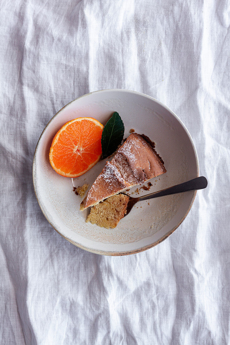 From above appetizing sweet cake and ripe orange mandarin cut and served on white plate on table