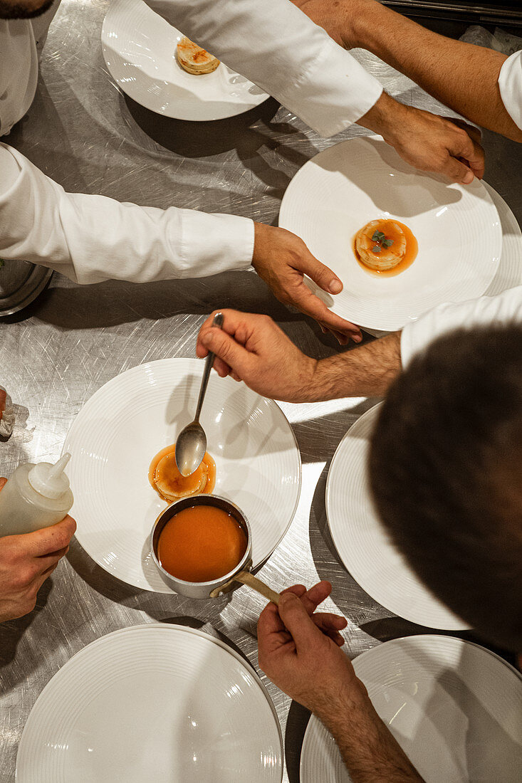 Unrecognizable male chefs putting sauce on top of exquisite dish while working in luxury restaurant