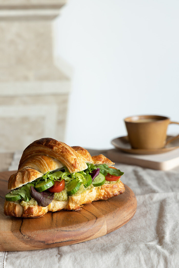 Tasty sandwich with fresh cucumbers and lettuce in plate placed on table with cup of coffee for breakfast
