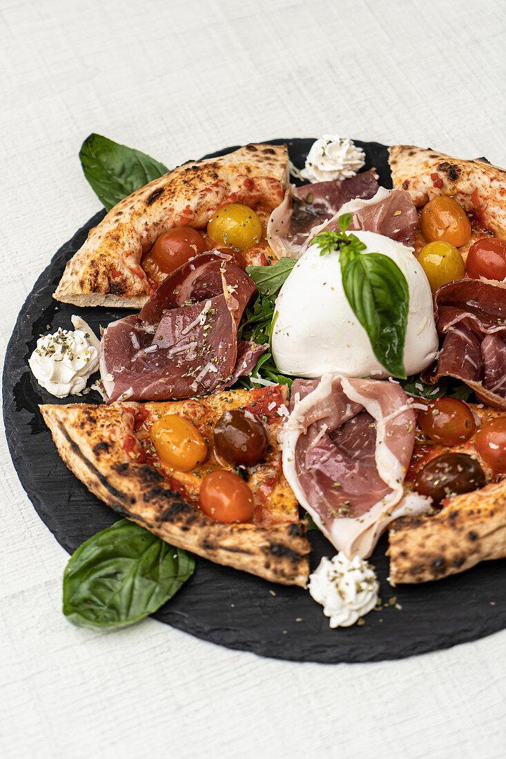 Italian pizza with small tomatoes and charred cornicione served with prosciutto and mozzarella