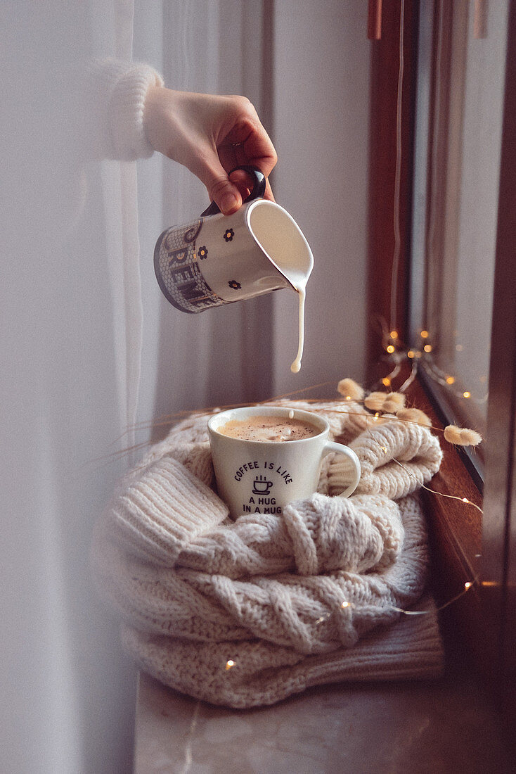 Woman pours milk into a cup of coffee Autumn climate