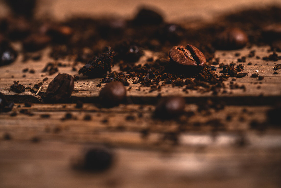 Aromatic roasted coffee beans placed on dark wooden table near spread fresh instant ground coffee