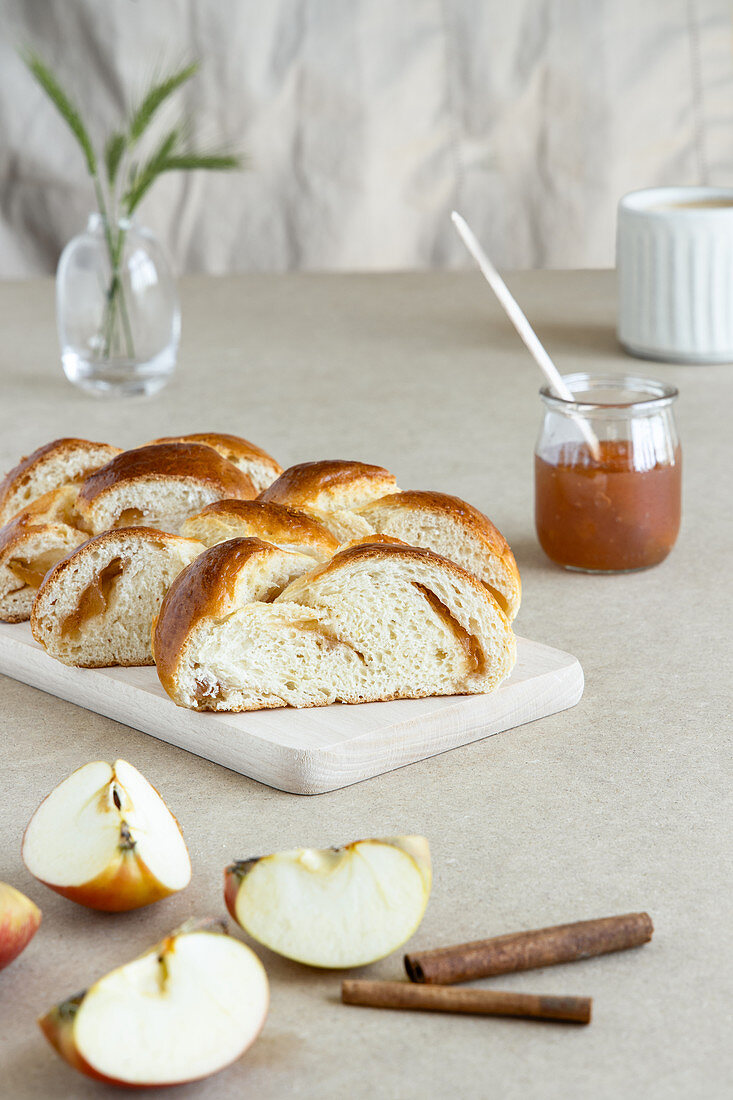 Fresh brioche made from butter dough with jam on wooden board next to glass jar of jam