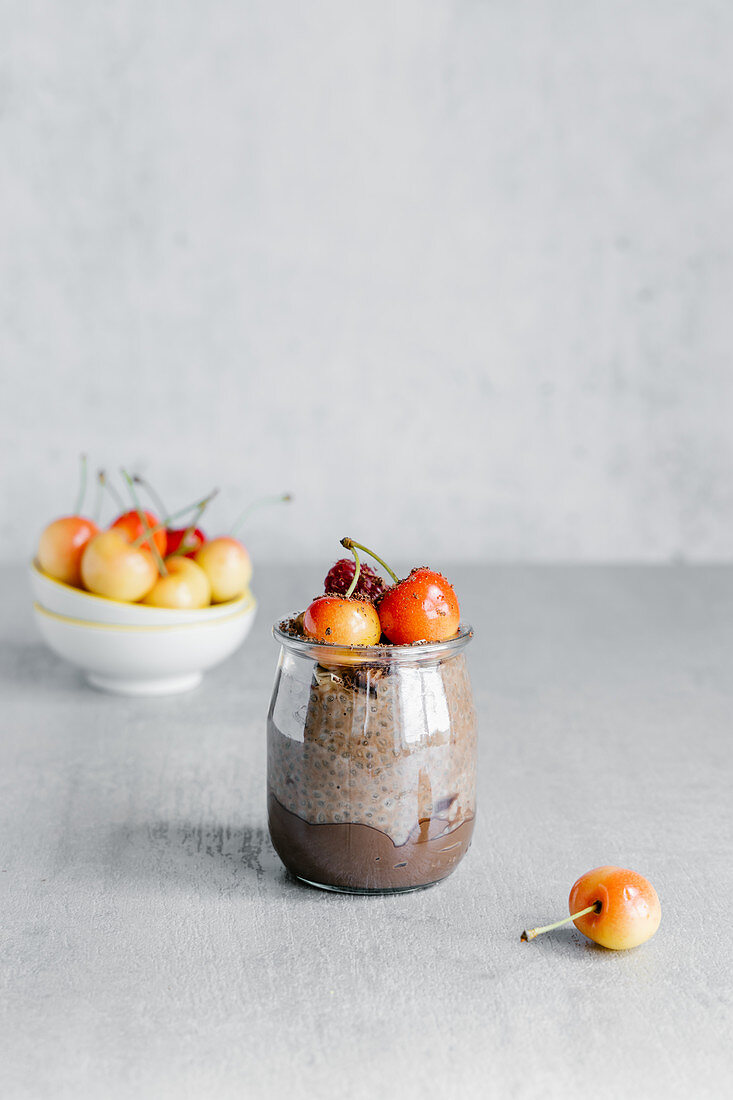 Glass jar with chocolate pudding consisted of yogurt and chia seed and garnished with white cherry