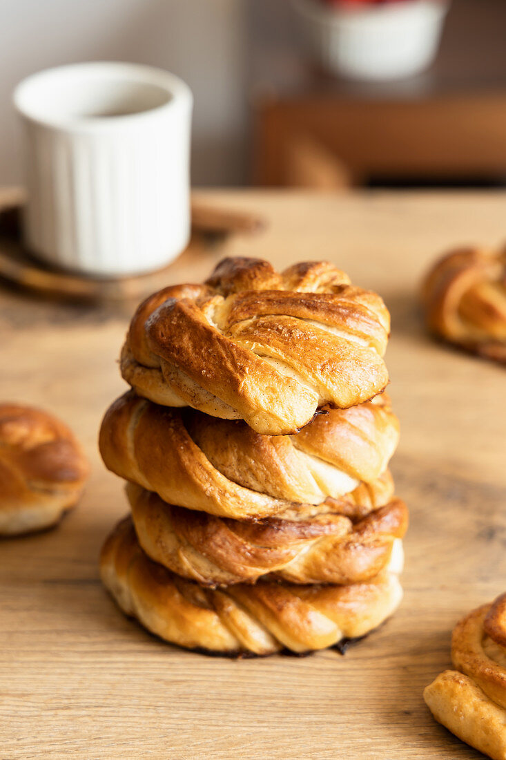 Stack of tasty cinnamon rolls placed on wooden table with cup of coffee in kitchen