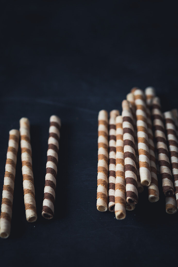 Waffer roll cookies on a dark surface