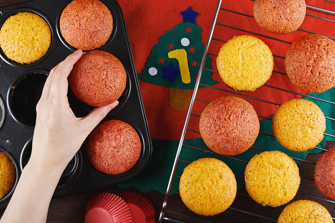 Crop anonymous female putting freshly baked colorful cupcakes from baking pan on metal grid while preparing pastry for christmas party
