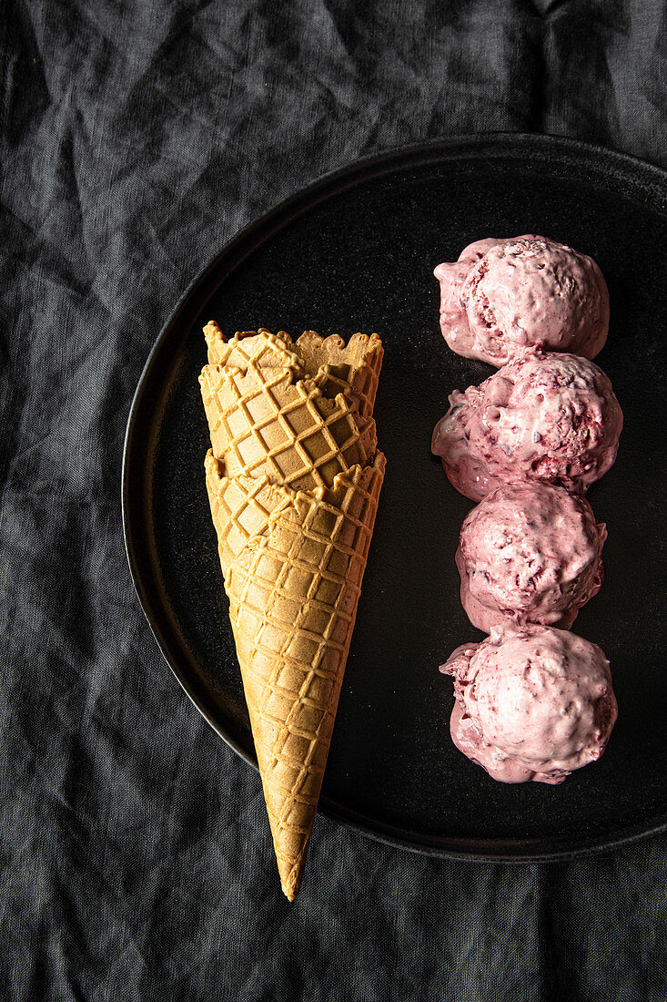Homemade cherry ice cream scoops arranged on table with waffle cones