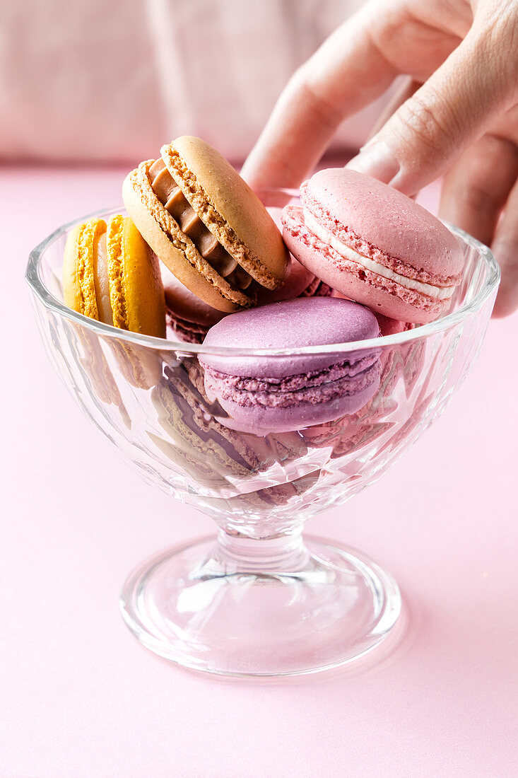 Crop female taking colorful tasty macarons from glass bowl placed on table in kitchen