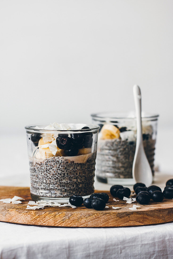 Glass jars with delicious chia puddings made of fresh tasty almond milk and chia seeds with honey topped with blackberries and sliced banana