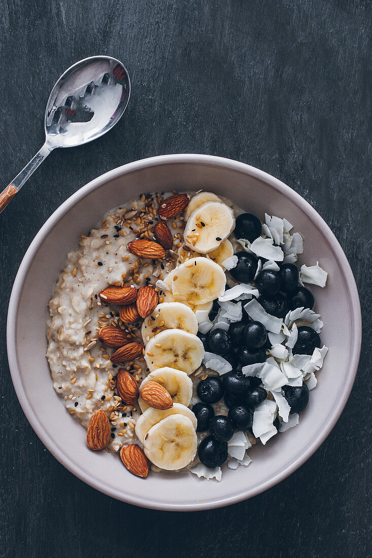 Bowl of porridge with raw almonds, sliced banana, blueberries and grated coconut