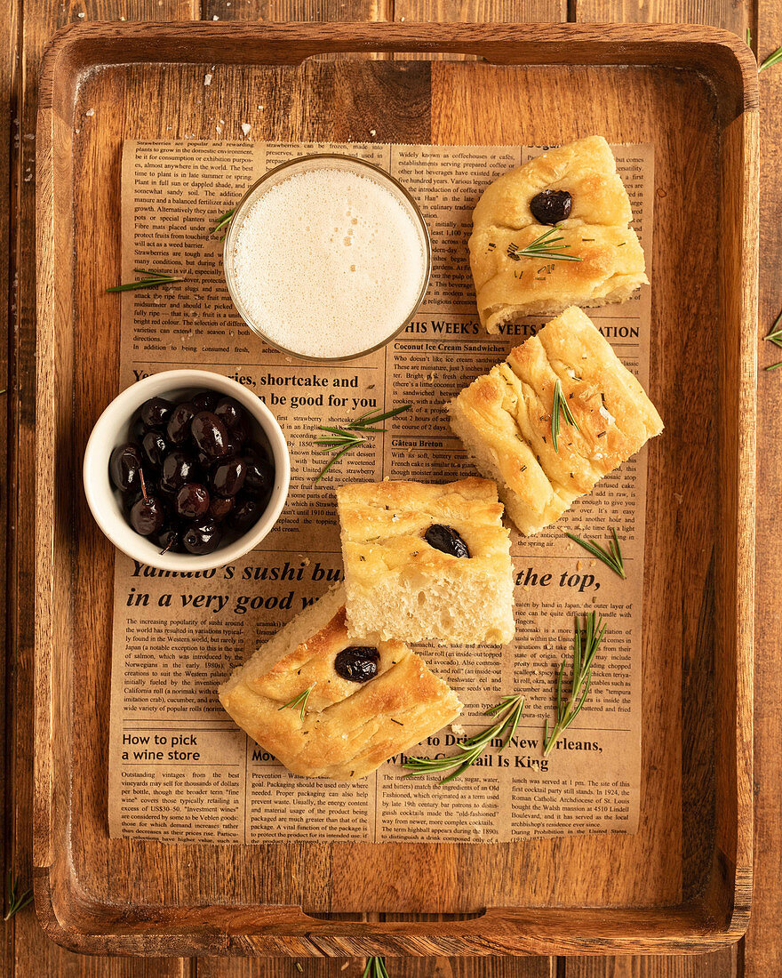 Focaccia bread served with black olives and glass of cold beer on wooden tray