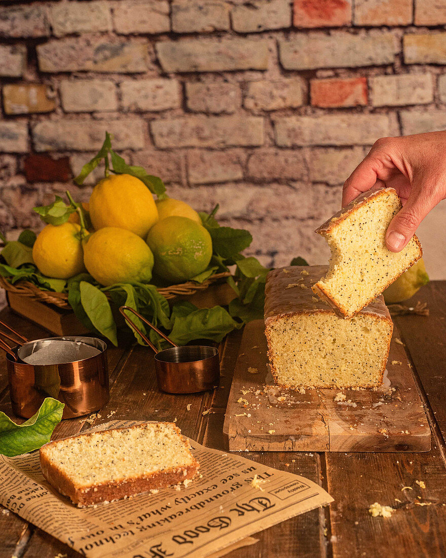 Lemon and poppy seeds cake with missing bite over table with cake and fresh whole lemons