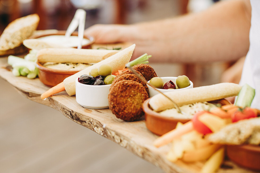 Crop anonymous person holding rustic wooden tray with various types of appetizers during party