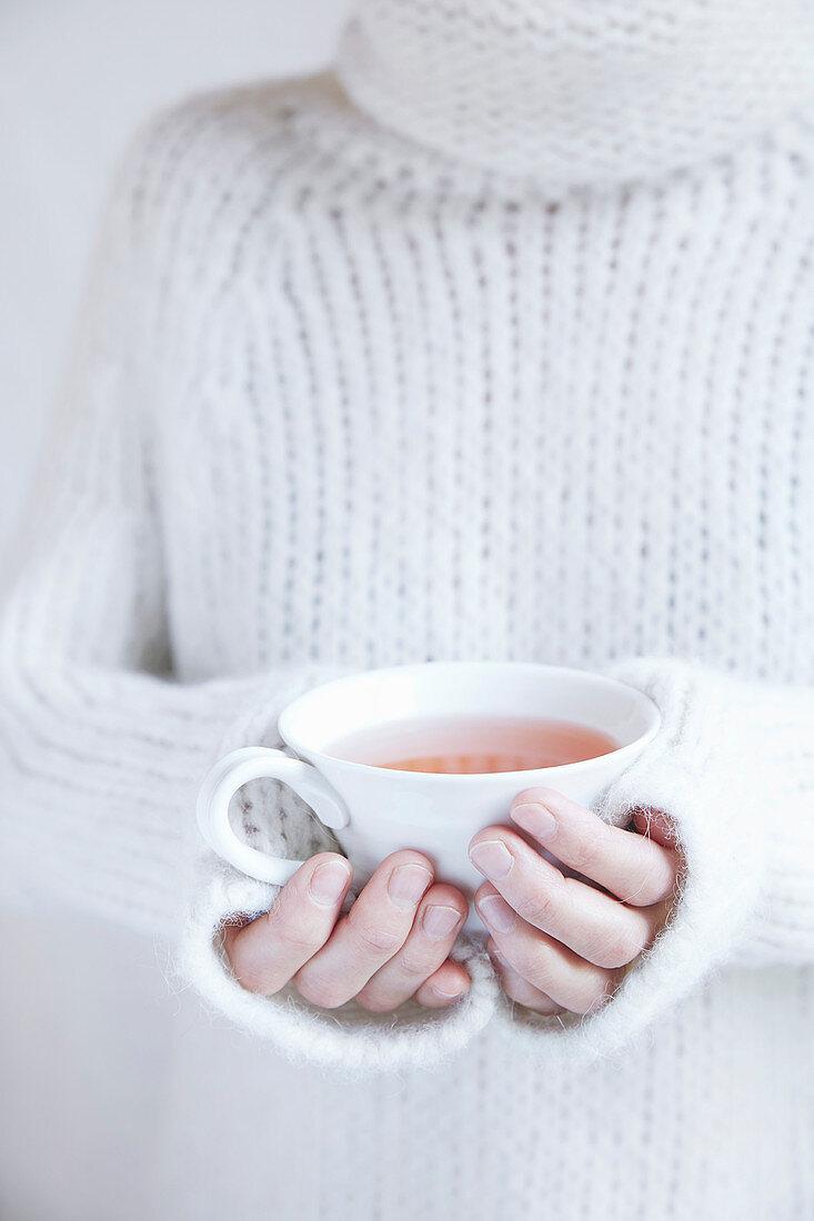 A woman holding a cup of Yogi tea