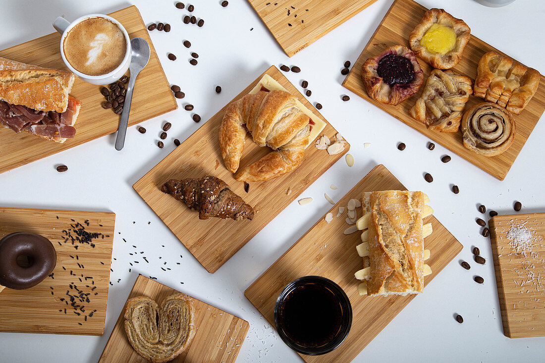 Breakfast table full of assorted pastries, sandwiches and coffee served