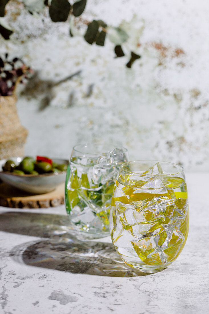 Large glasses of mojito cocktail with mint leaves and ice cubes put on concrete surface