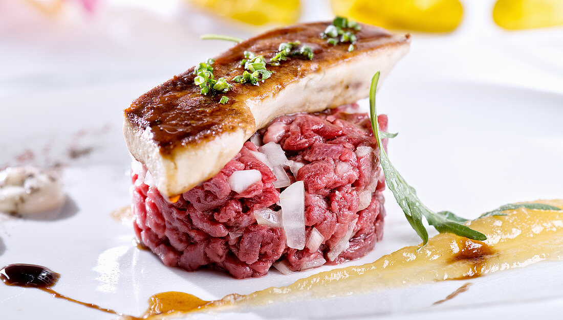 Juicy steak tartare with white onion served with glazed piece of foie gras on white plate with sauces