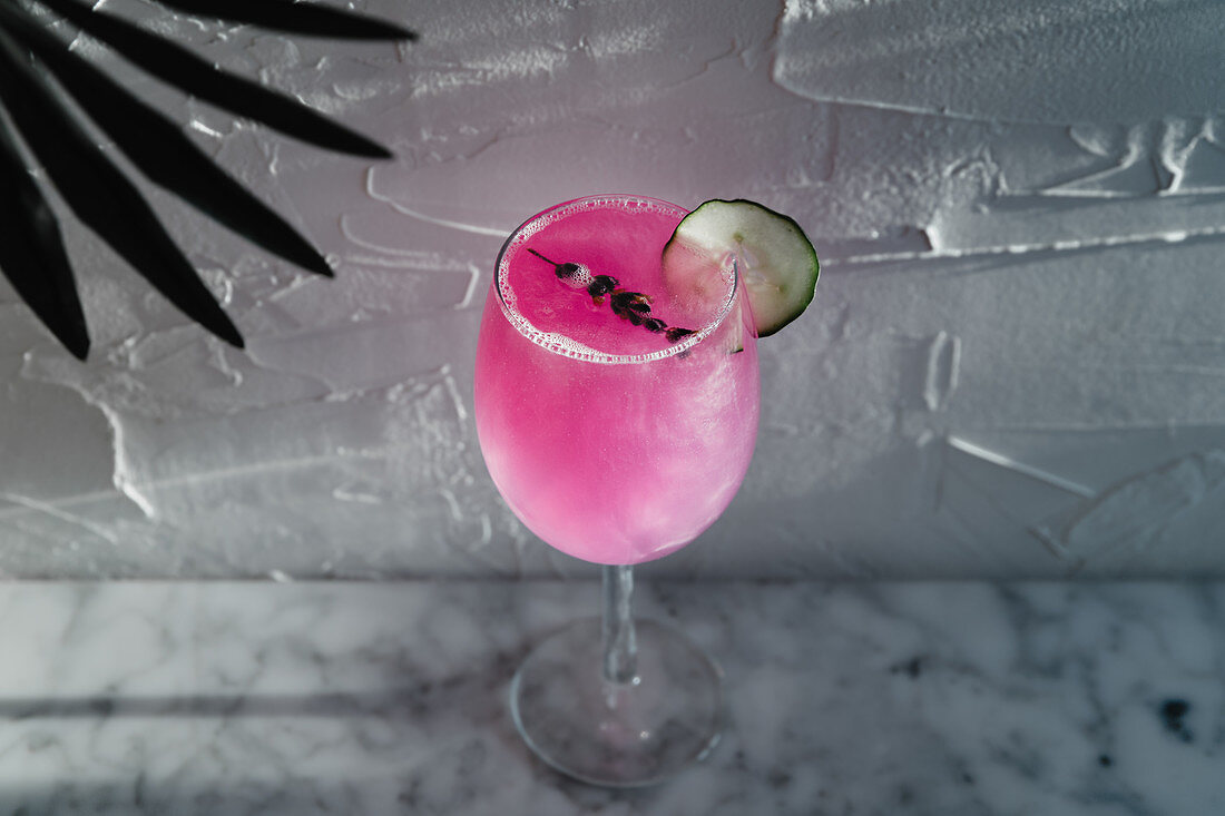 Purple cocktail garnished with herbs and sliced lime