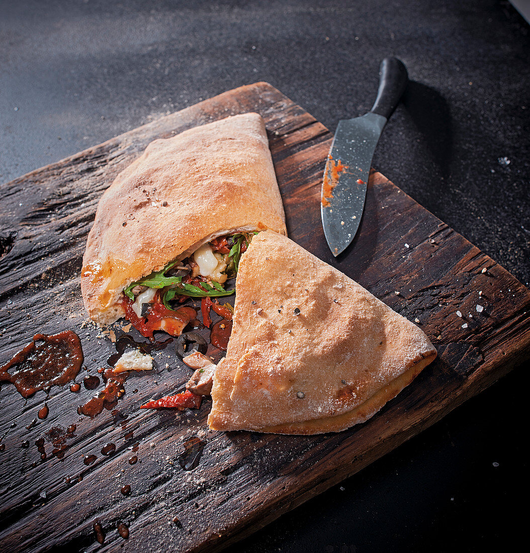 Calzone with porcini mushrooms, olives, sun-dried tomatoes and scamorza