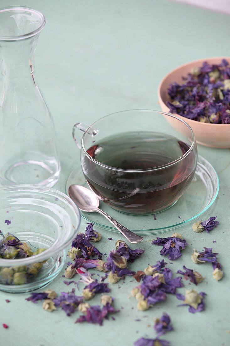 Cold extraction of mallow blossoms in a glass cup next to dried blossoms