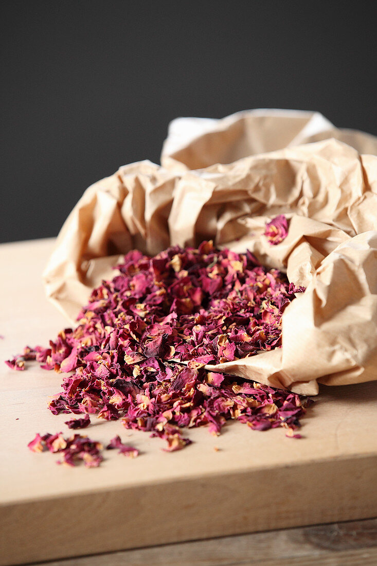 Dried rose petals in and next to a paper bag
