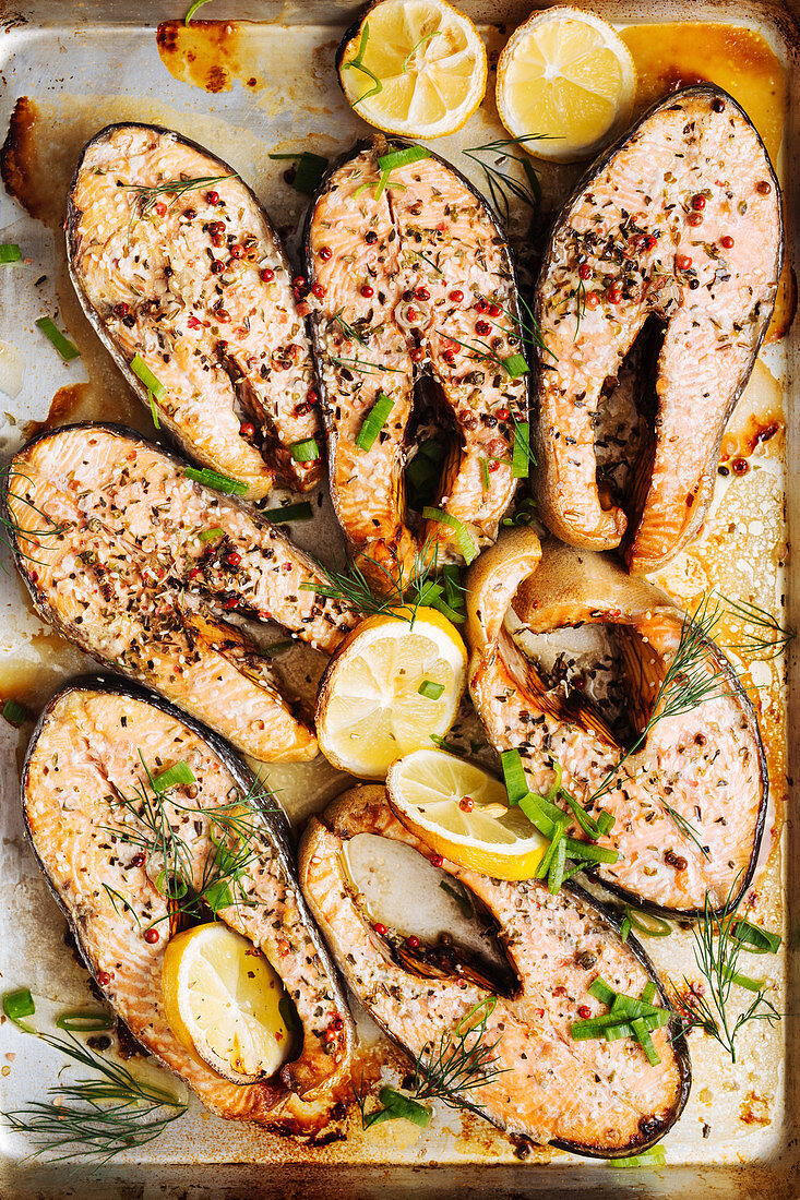 Roasted salmon steaks with aromatic herbs and spices garnished with lemon slices on metal baking tray