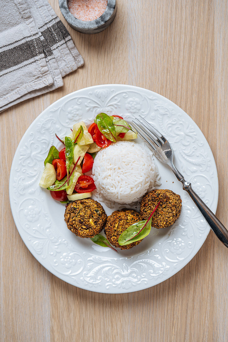Vegan cutlets served with white rice and fresh vegetable salad on wooden table