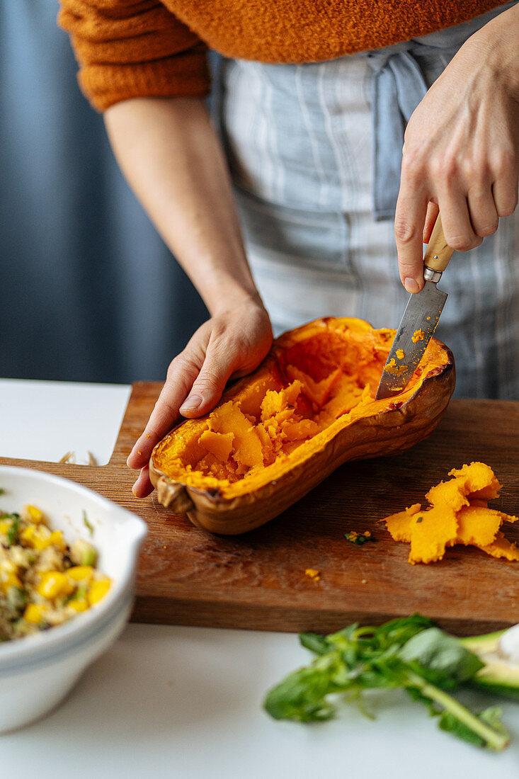 Woman preparing pumpkin for filling