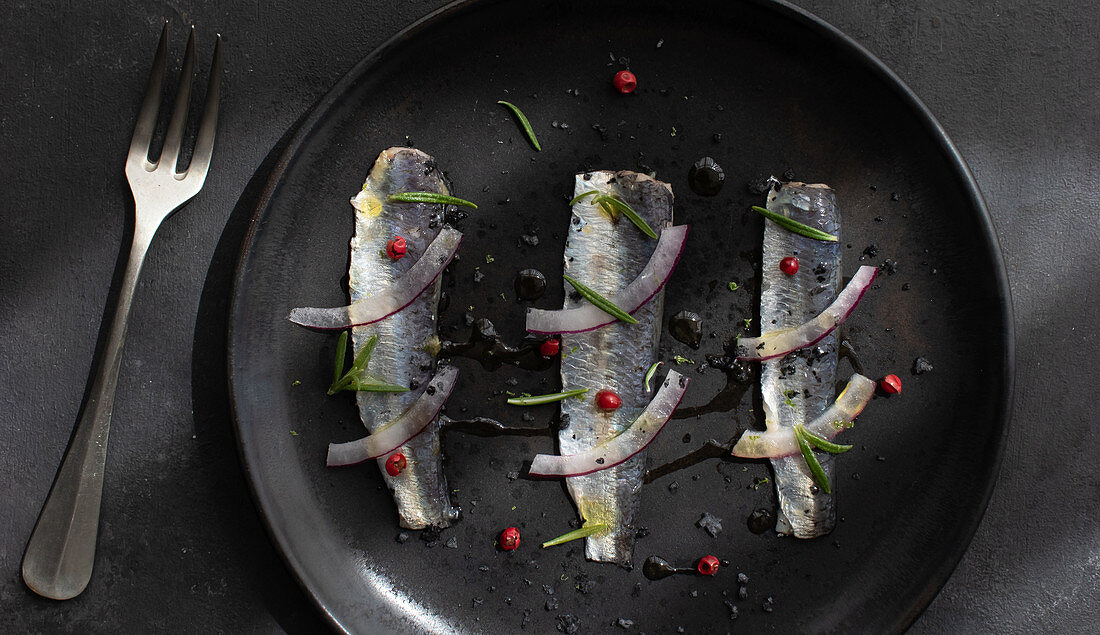 Marinated sardines fish fillet with onion and herbs