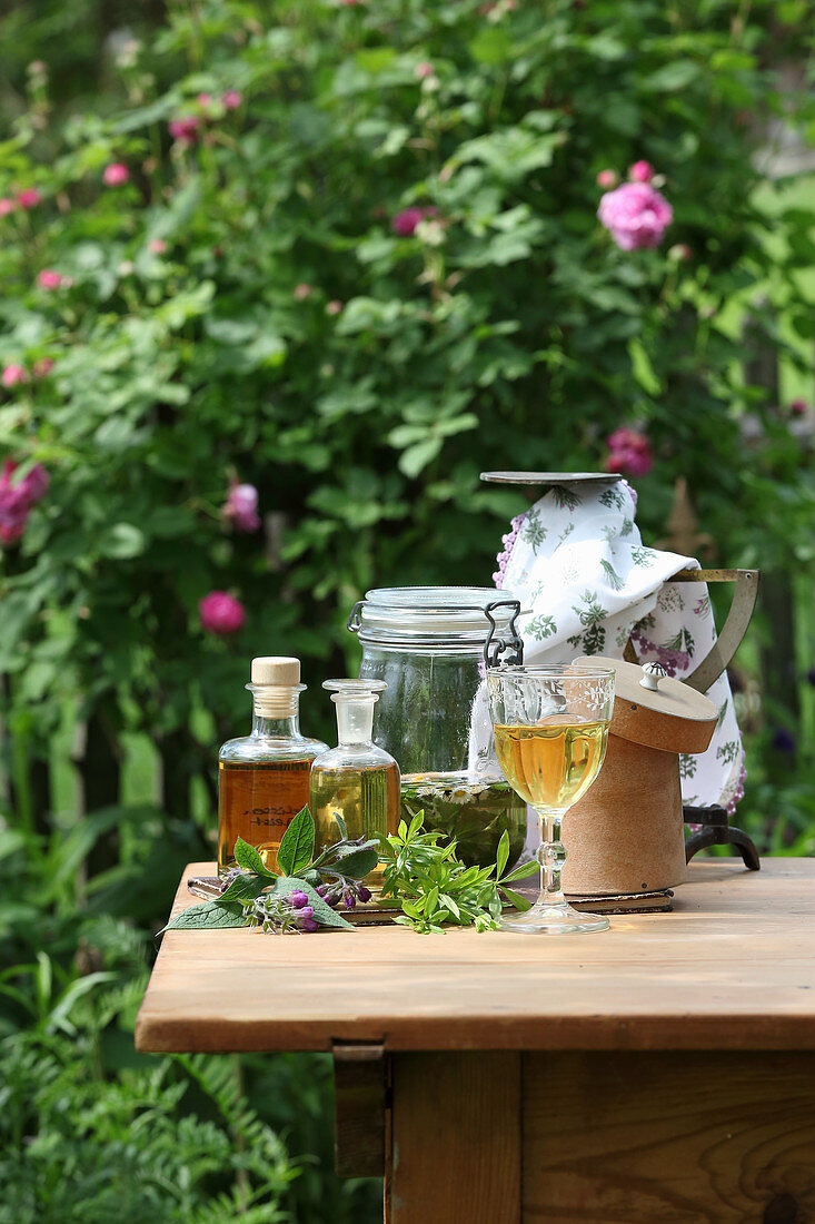 Different tinctures with herbs on a garden table