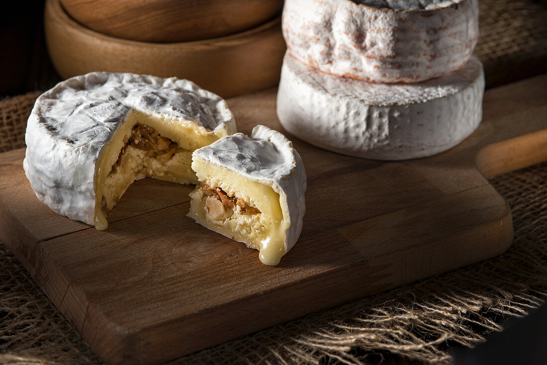 Brie cheese filled with nuts and raisins, sliced