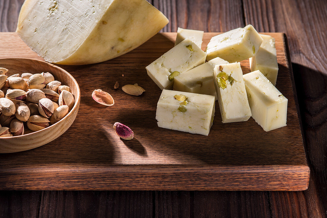 Soft cheese with pistachio nuts, in one piece and diced