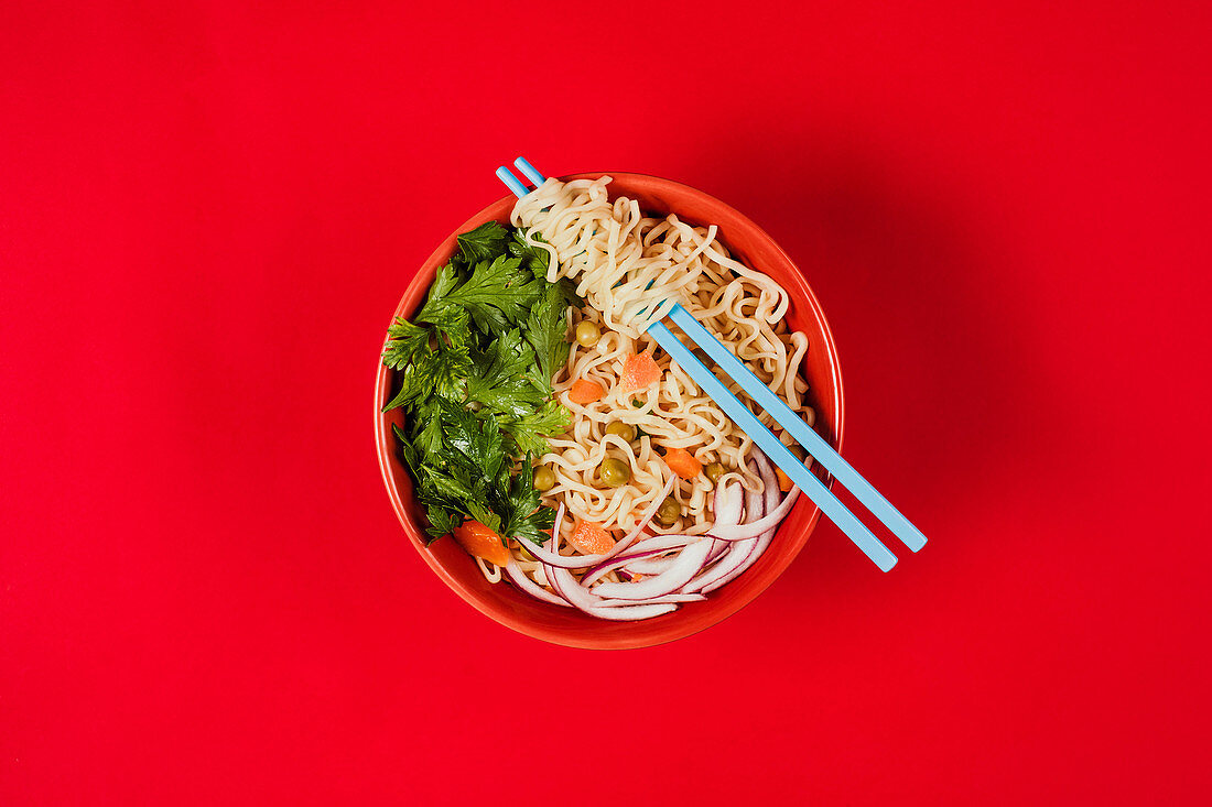 Bowl with noodles, onion, carrot slices and fresh parsley