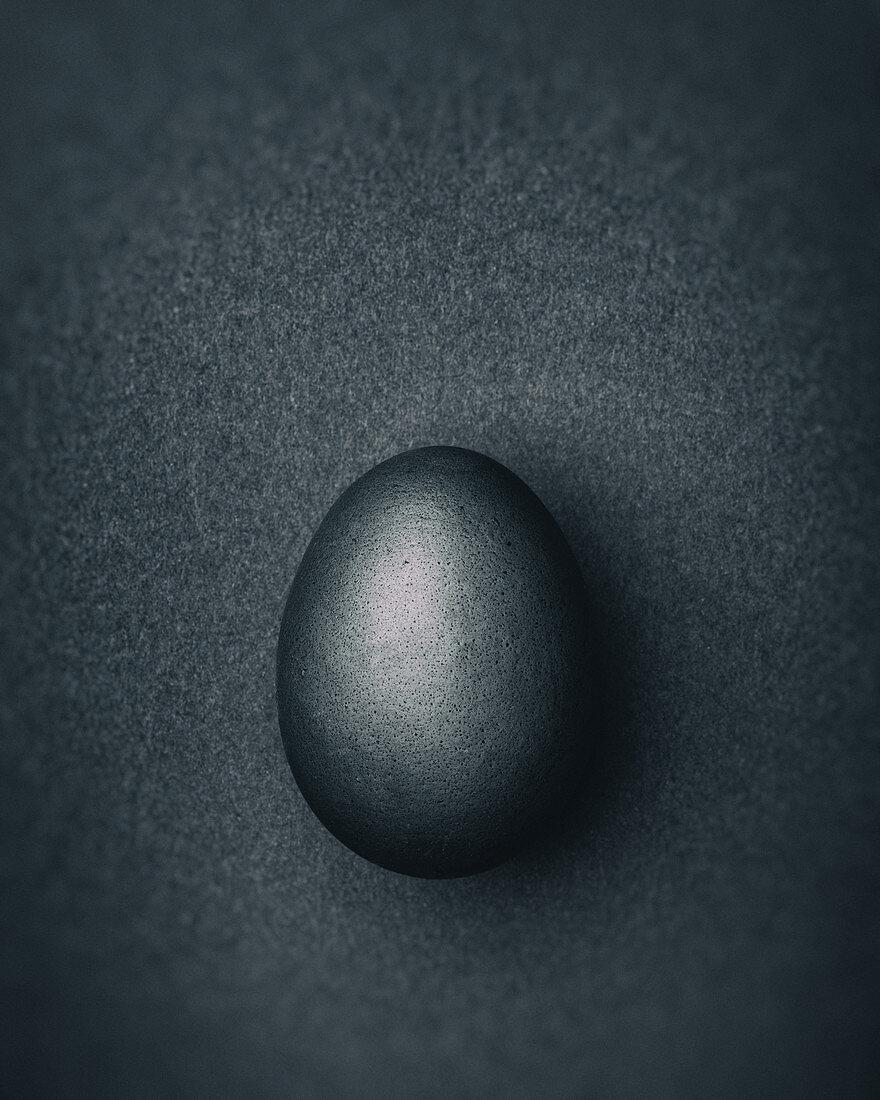 Dark gray Easter egg on a dark gray background