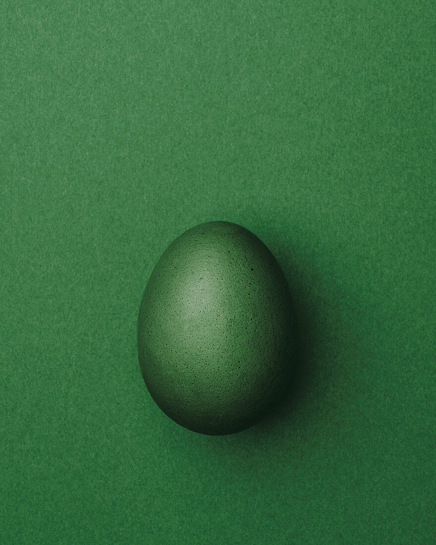 Green Easter egg on a green background