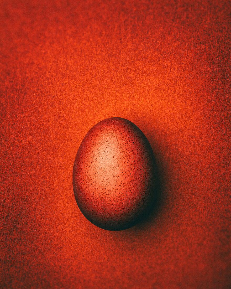 Dark orange Easter egg on a dark orange background