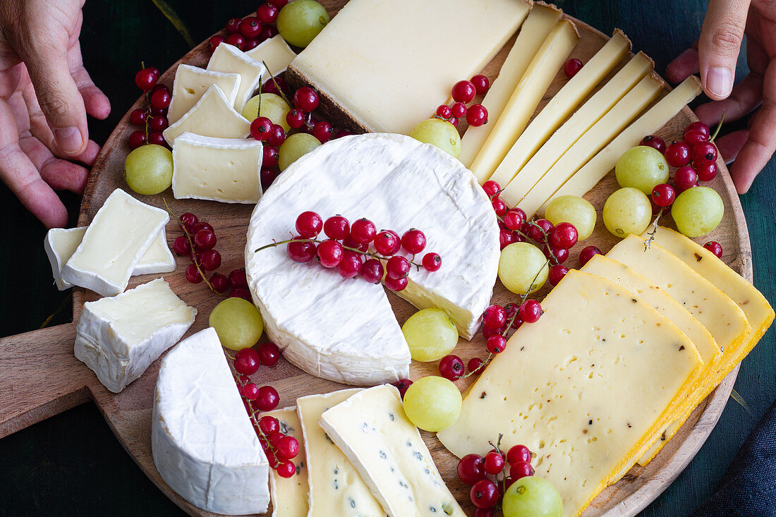 Cheese platter with sweet grapes and red currants on wooden plate