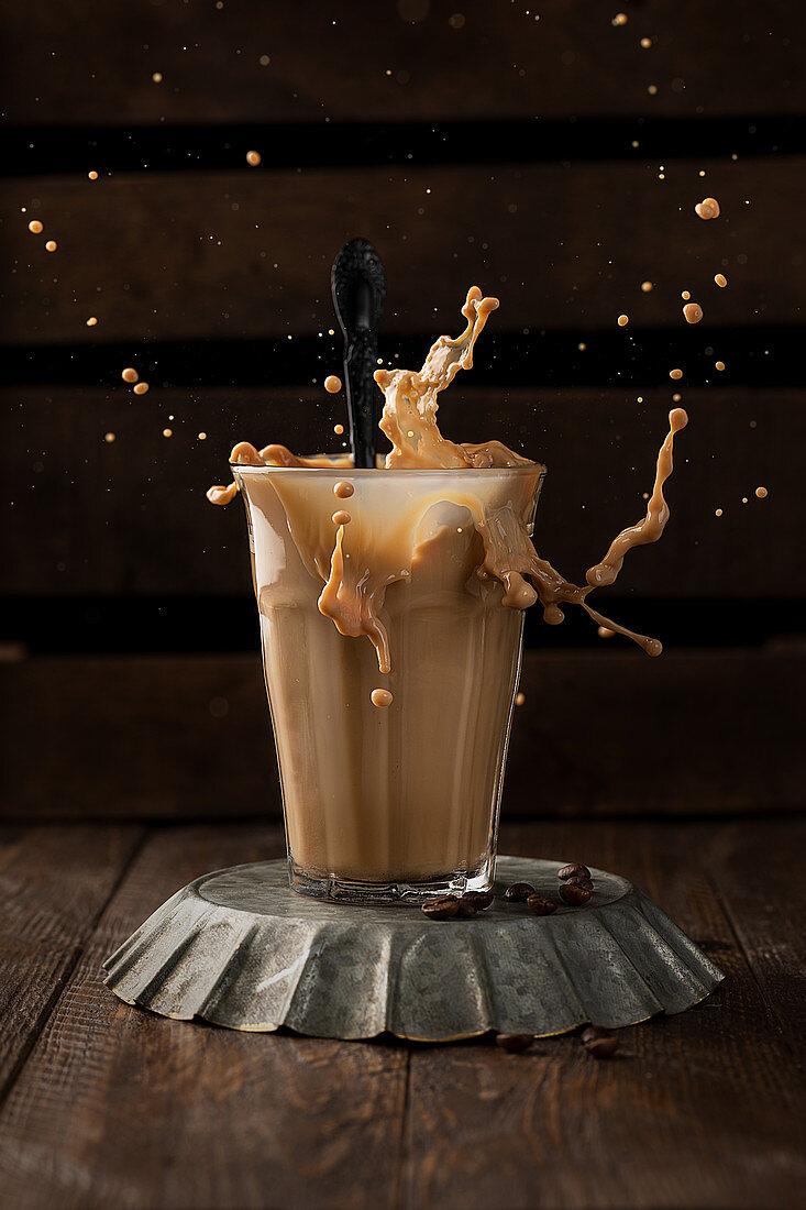 Glass of aromatic coffee with milk splashing