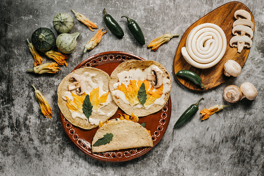 Tortillas with melted cheese and squash flowers near mushrooms and green chili peppers