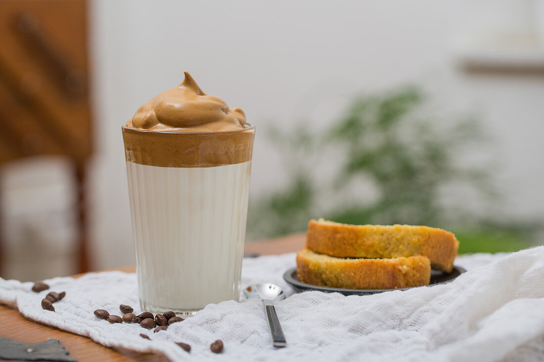 Glass of Dalgona coffee with whipped instant coffee and milk