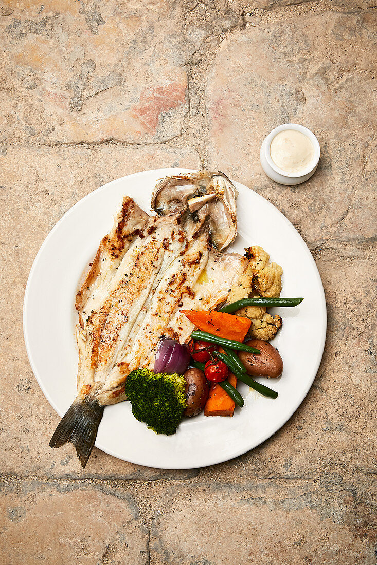 A whole fried bass with coriander mayonnaise and vegetables