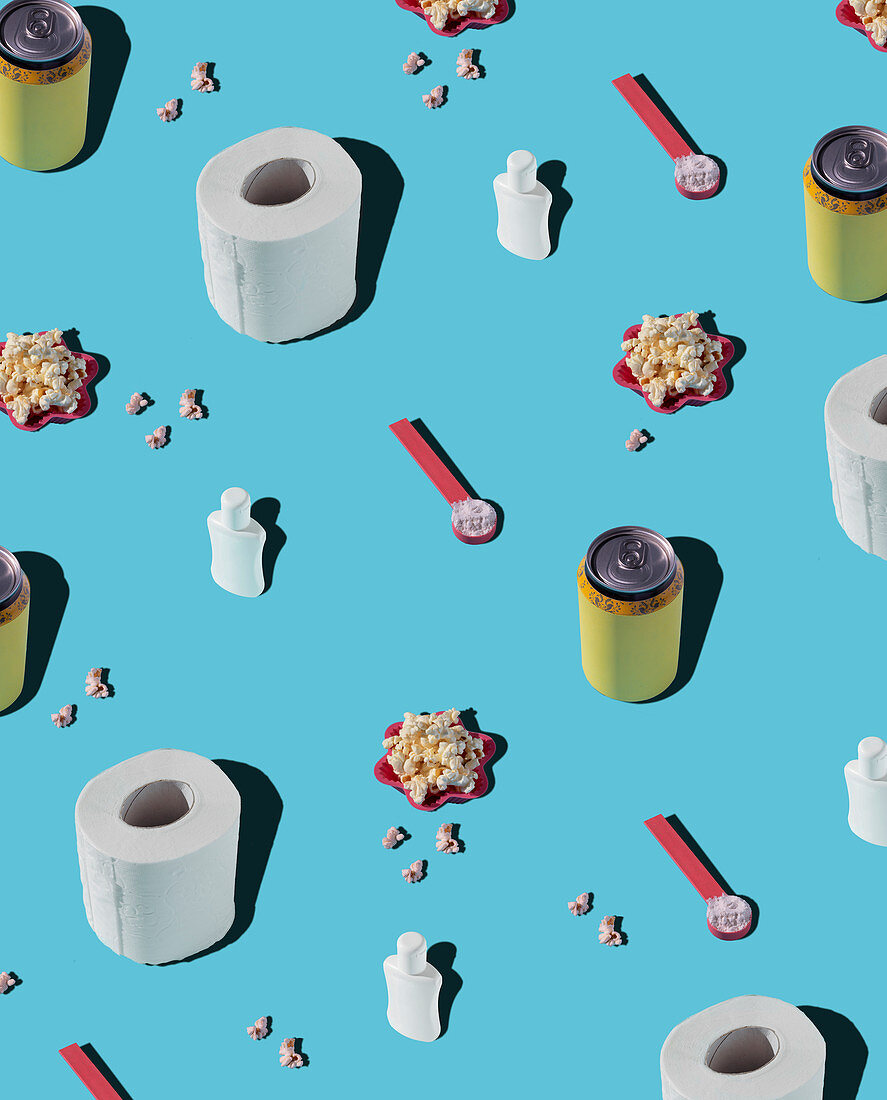Patterns of hygiene supplies and soda cans on blue background with popcorn
