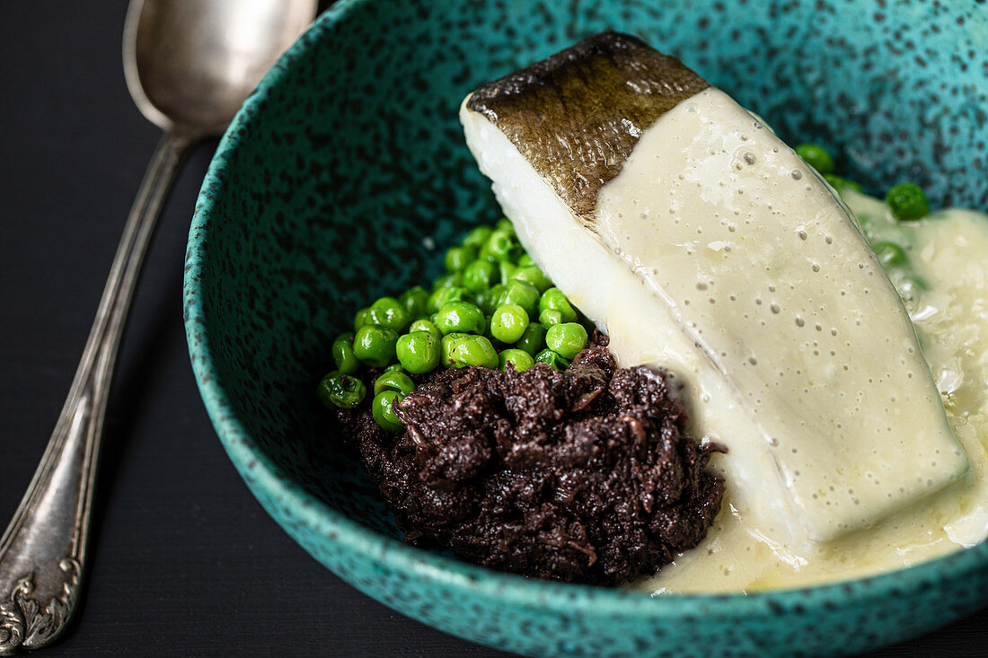 Cod fish with green peas and cream sauce in bowl