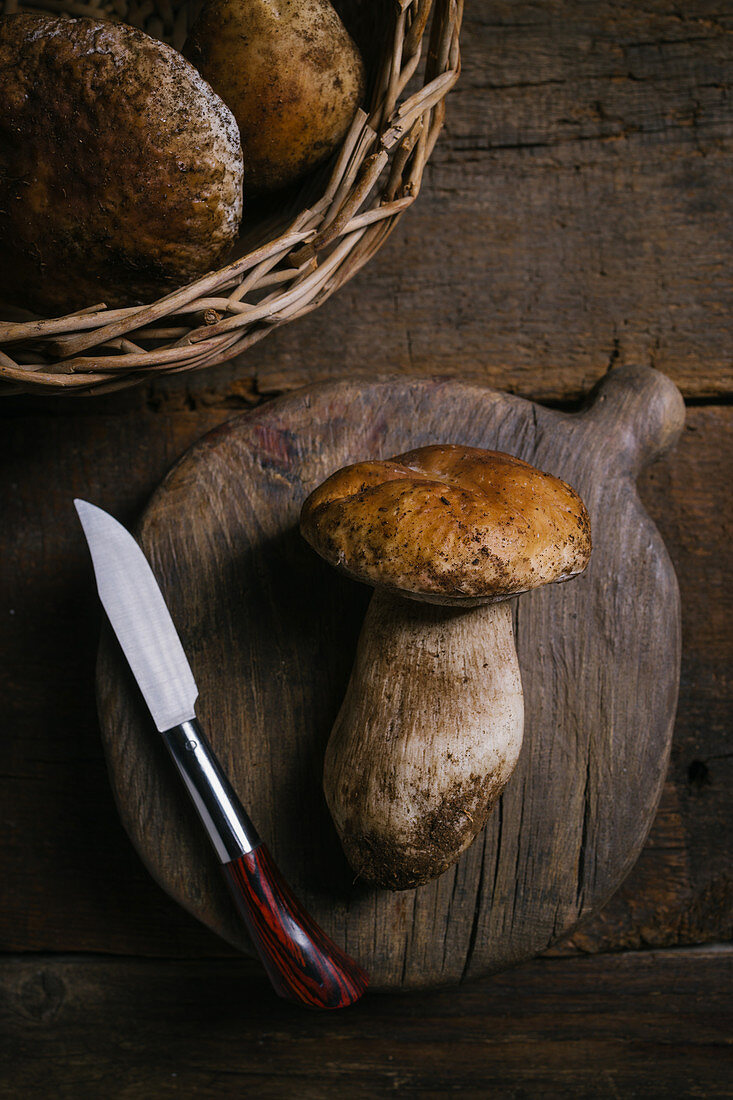 Raw whole porcini with knife and cutting board