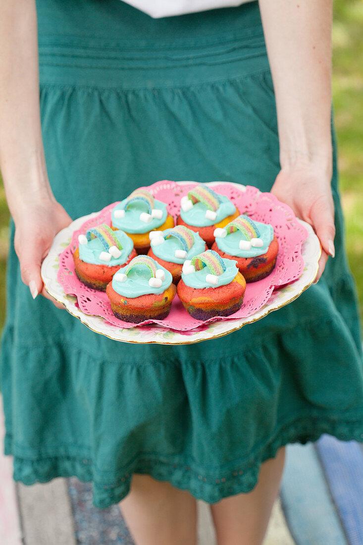 Frau hält Teller mit bunten Muffins mit Regenbogen-Deko
