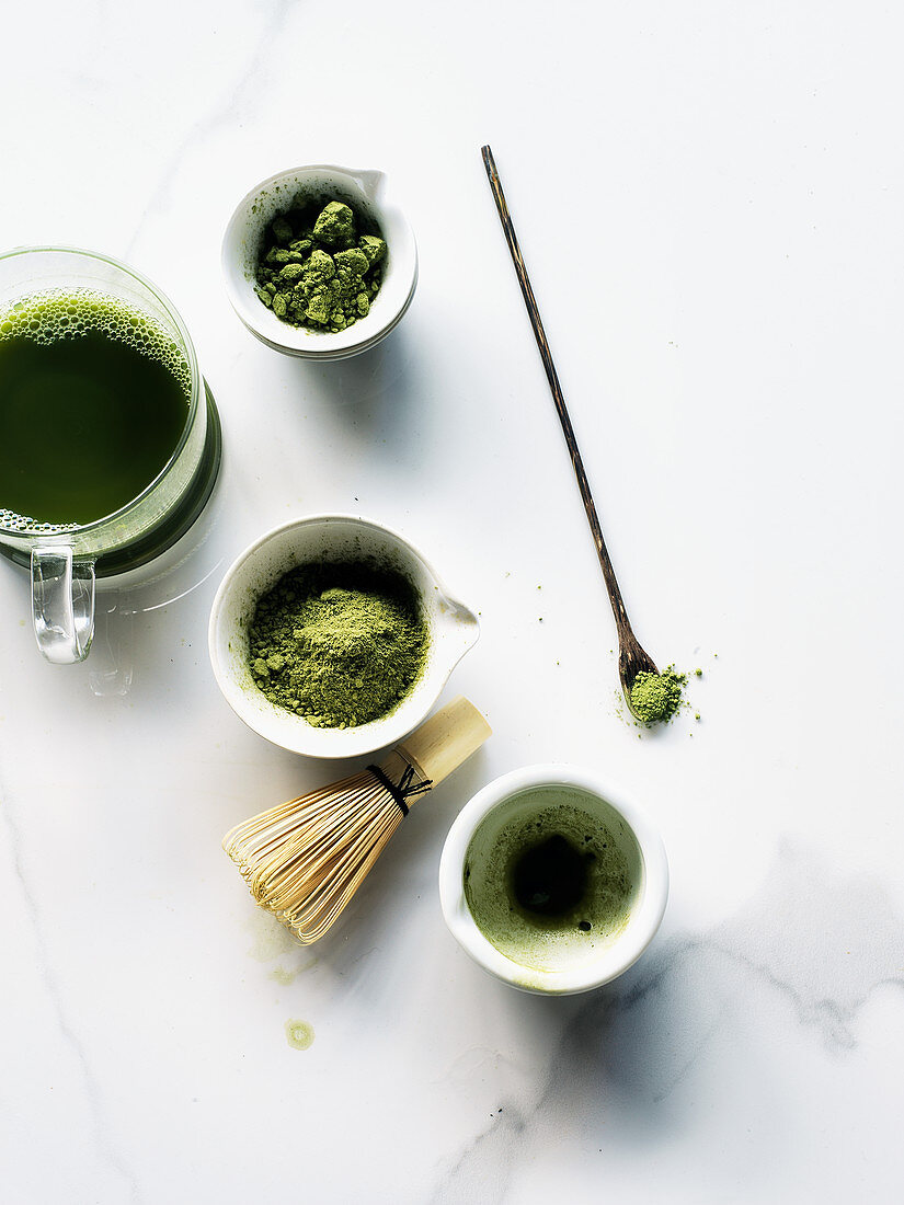 Three cups of Matcha tea and powder with whisk