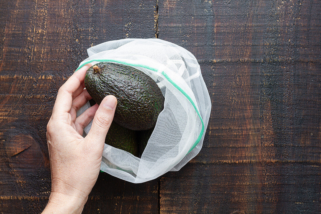 Person taking avocado from sack
